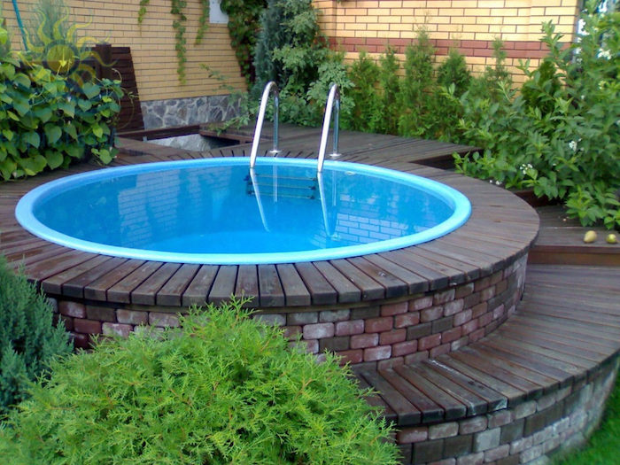 green shrubs and flowers, near a small, circular elevated pool, lined with bricks, and wooden planks, cool backyards