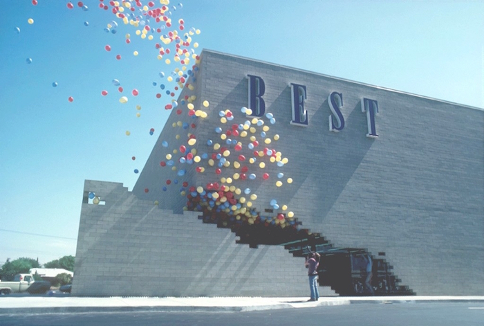 pale grey brick building, featuring the word best, written in large blue letters, on one of its walls, many balloons in different colors, flying out of a large crack in the building