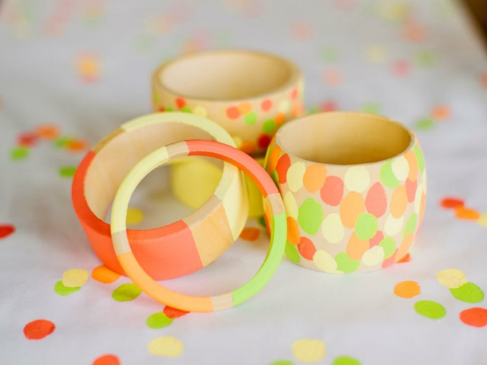 neon colored stripes, ad paint daubs, decorating five wooden bangles, with different shapes