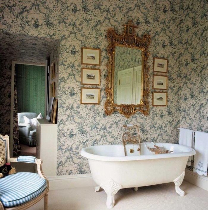 claw-footed antique bathtub in white, inside a room with a baroque-style, floral wallpaper in cream and green, mirror in ornate gold frame