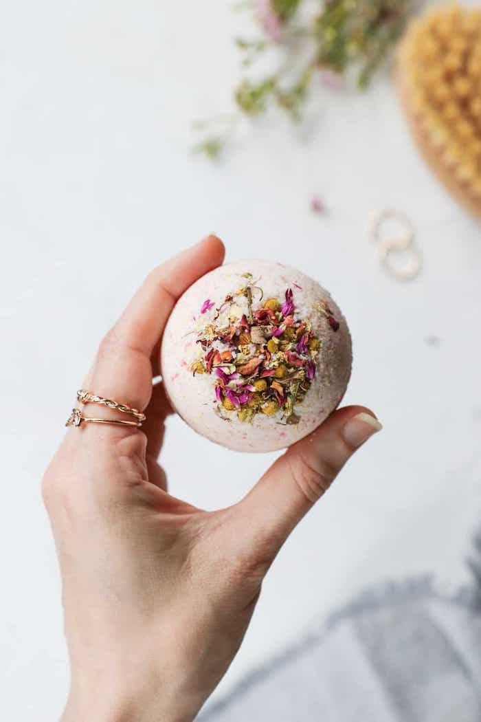 bath bomb with dried flowers inside, held by a female hand, wearing gold rings, creative diy christmas gifts