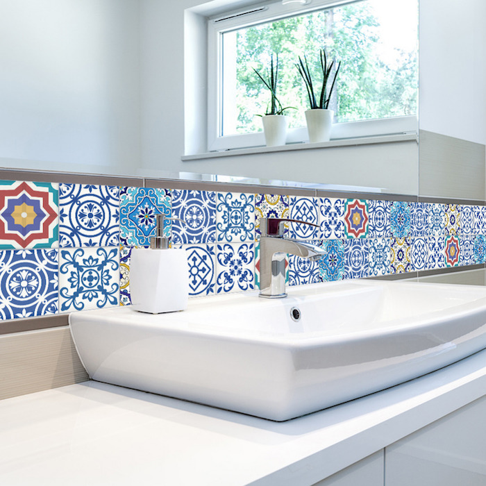patchwork of multi-coloured Moroccan tiles, near a large wall mirror, and a modern white stink, with a silver metal faucet, bathroom wall decor ideas, two potted plants in a window