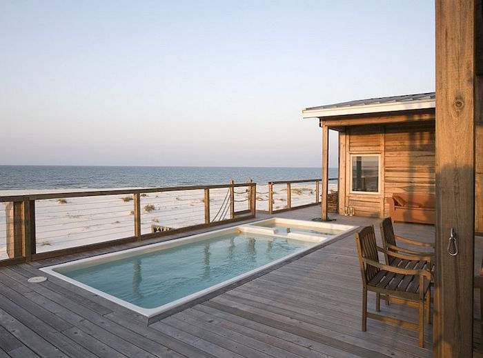 seaside bungalow made of wood, with a rectangular patio pool, white sand and sea nearby