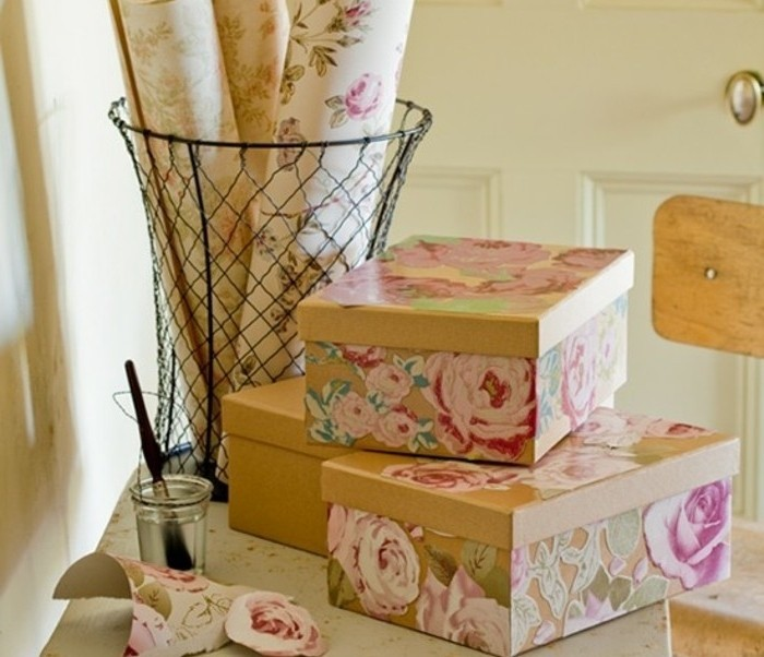 last minute birthday gifts, beige cardboard boxes, decorated with pink and green, floral paper decoupage, rolls of patterned paper, a jar with glue, and a brush nearby