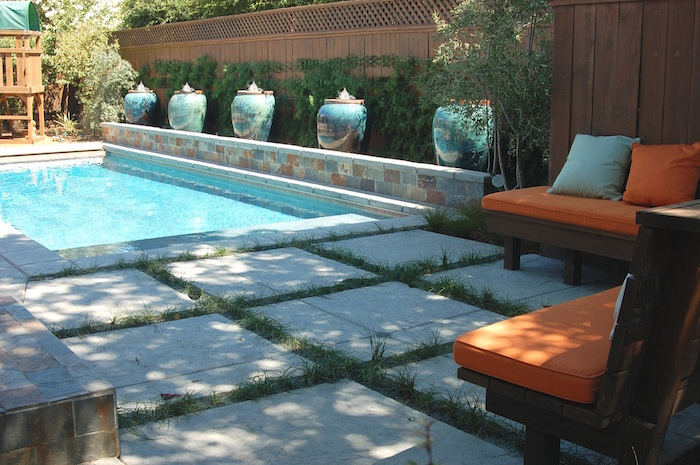 five large ornate vases, decorating a small wall, near a light blue pool, small inground swimming pools, garden with two wooden benches, covered in orange and pale blue cushions