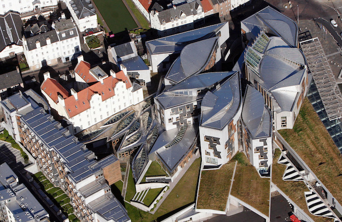 areal photo of the scottish parliament building, postmodern design, with several detached structures, each in an asymmetrical shape, with a grey roof