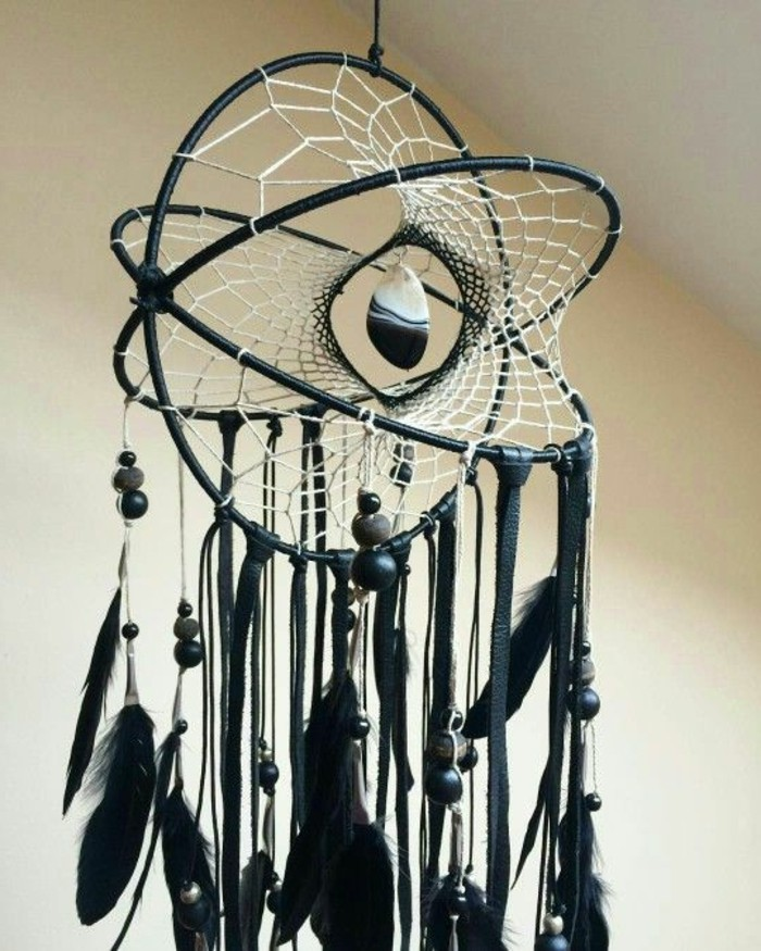 four dimensional dream catcher, in black with a white net, decorated with multiple black feathers, a black and white stone, and dark grey and black beads