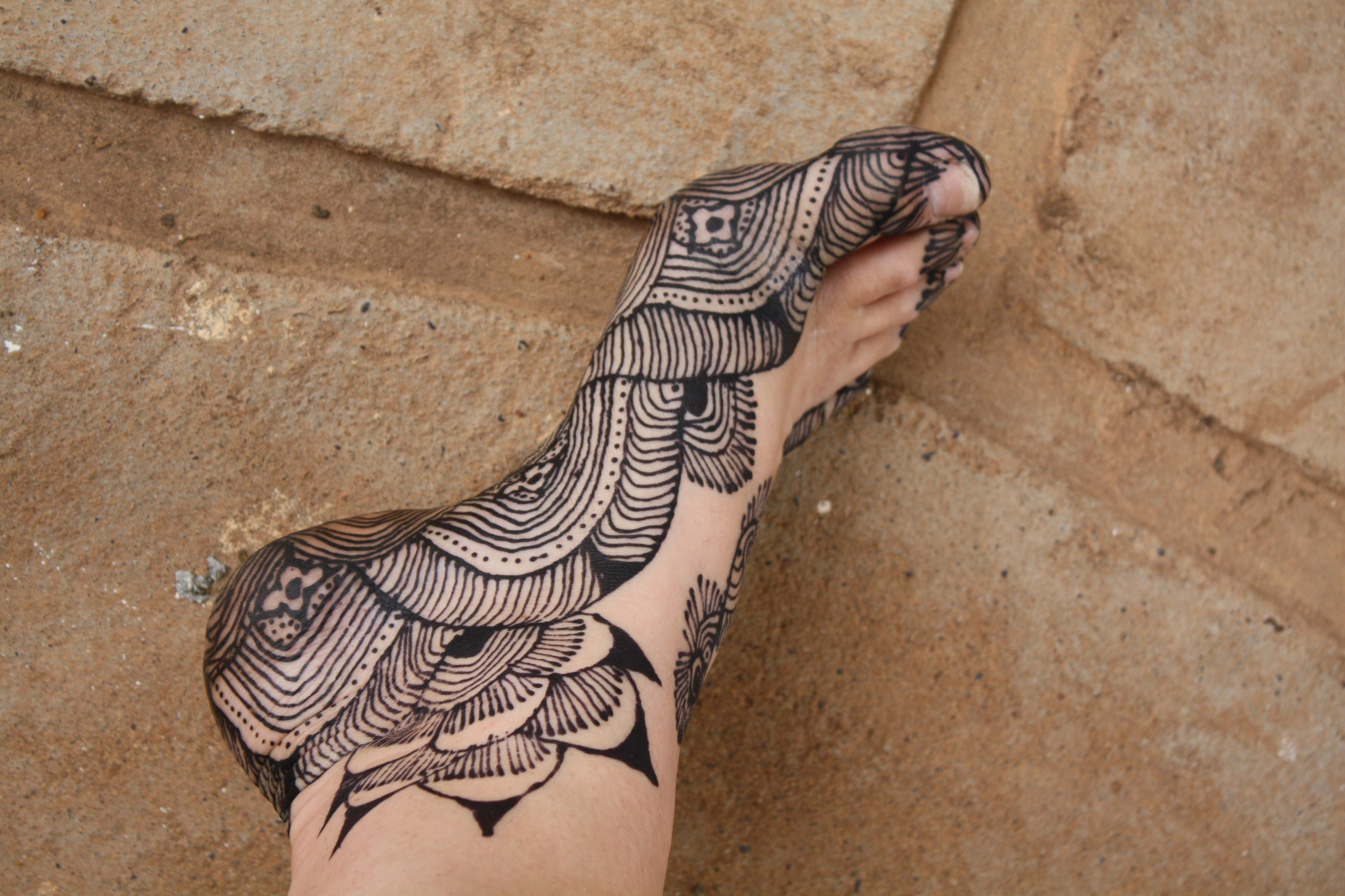 ornamental black henna tattoo, on the sole and ankle of a leg, resting on the ground, temporary henna tattoos