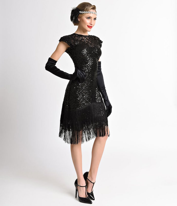 sequined shimmering black flapper gown, with fringed hem, worn by a brunette woman, with black t-bar shoes, and long black gloves, gatsby dress
