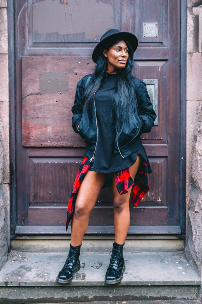 90s outfit ideas, black leather jacket, worn by a black woman, with long black hair, a black t-shirt, and a red flannel shirt, tied around waist