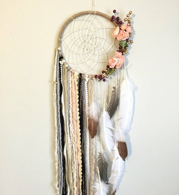 boho-style dreamcatcher, decorated with multiple crochet lace strips, feathers and flowers, how to make a dreamcatcher, hanging on a cream wall