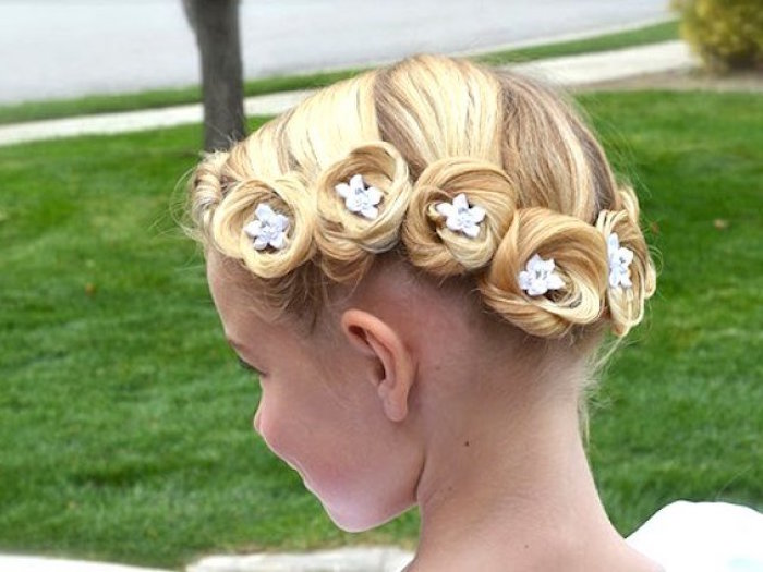 swirls of blonde hair, decorated with tiny, white blossom ornaments, on the head of a small child, flower girl hairdos