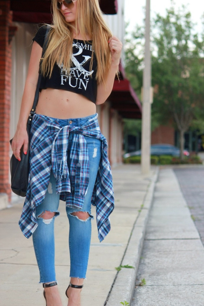 90s clothes womens, cropped black t-shirt, with white print, ripped jeans and a flannel shirt, tied around the waist