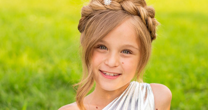 honey blonde child, with long curled side bangs, and a crown braid, cute girls hairstyles, smiling in a silver, one-shoulder dress