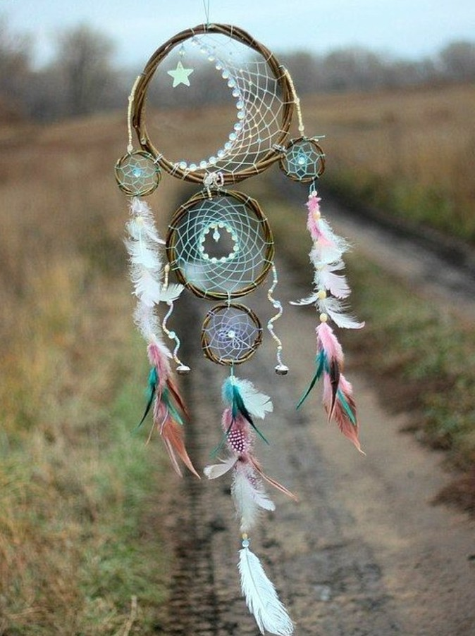 star ornament and lots of feathers, in pale white, pink and blue, decorating a handmade dreamcatcher, with three nets