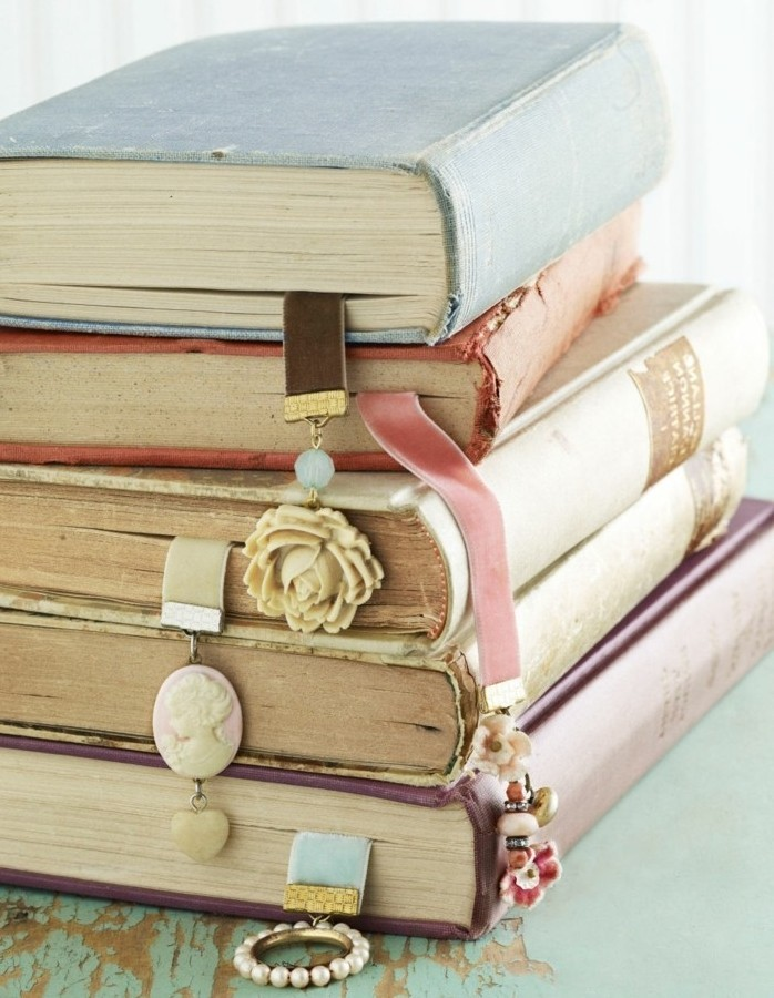 stack of vintage books, most containing diy bookmarks, made with suede straps, in different colors, and jewelry-like charms, last minute birthday gifts, cameo brooch and rose ornament