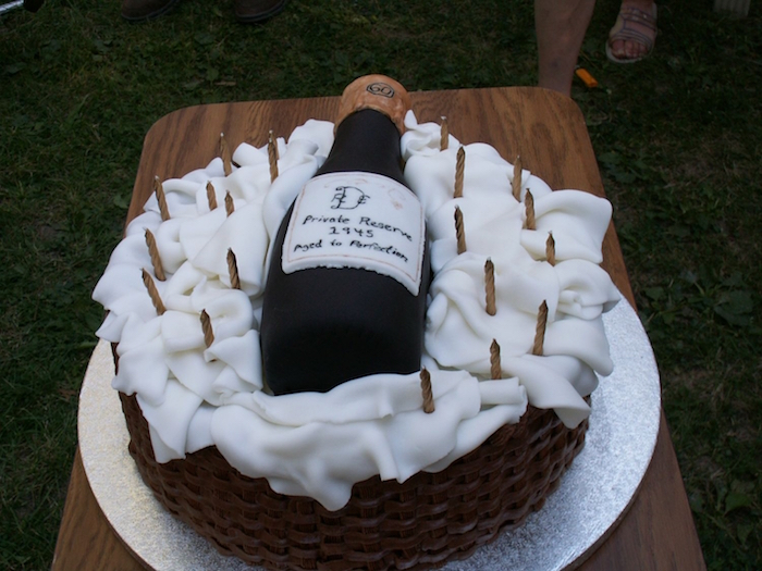 wine bottle-shaped cake in black, with a white label, placed on a basket made from fondant, unusual birthday cake ideas