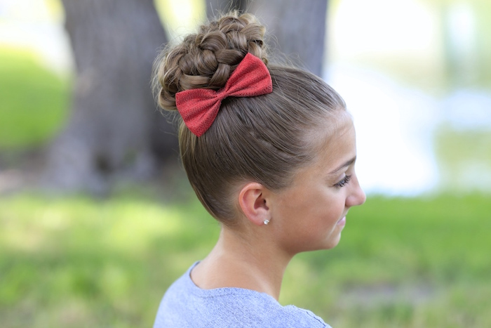 cute hairstyles, braided hair bun, on a brunette child's hair, decorated with a red bow