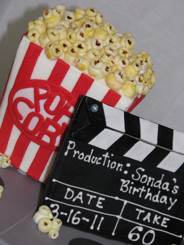 cake shaped like a vintage popcorn box, in red and white, behind a black clapper board, both made from colorful fondant, 60th birthday party ideas, film-themed cakes