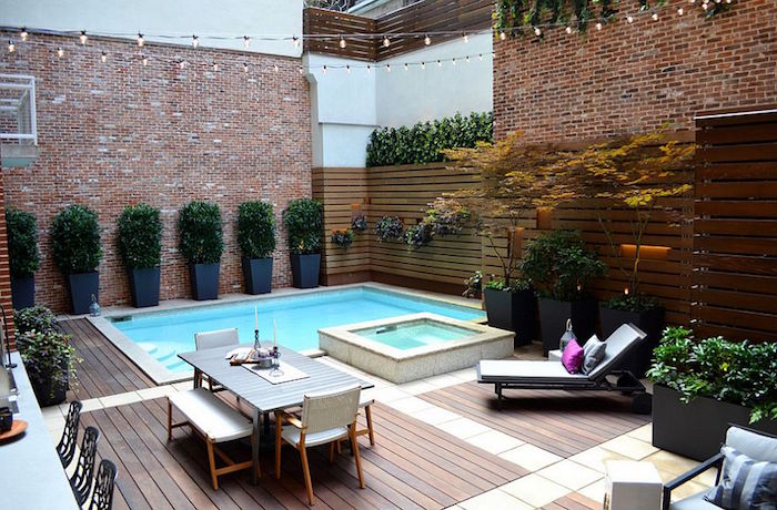 shrubs planted in pots, near two small pools, in a yard surrounded by brick walls, and containing a table with chairs and benches, cool backyards, sun bed with cushions