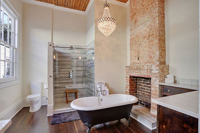 lit crystal chandelier, hanging over a black and white bathtub, in a room with a vintage wooden floor, containing a toilet, a shower cabin, and a fireplace