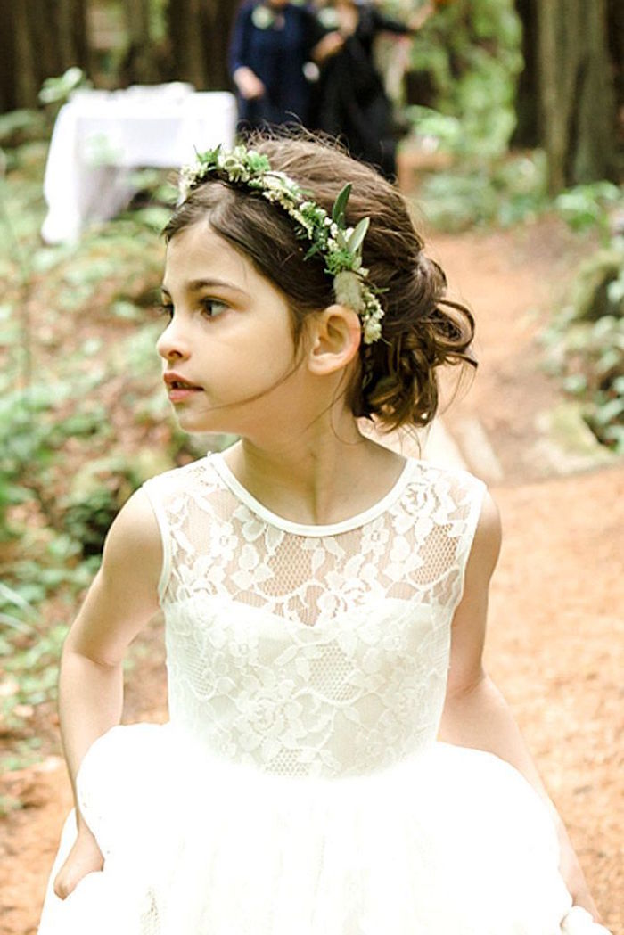 lace and tulle dress in white, worn by a small flower girl, with brunette hair, done in a curly half up-do, and decorated with a flower wreath