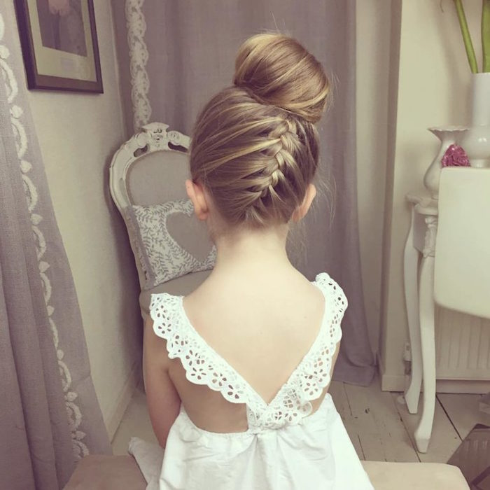 back view of a braided hairstyle, with a blonde side braid, and a bun on top of the head, worn by a small child, in a white summer dress