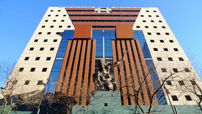 woman holding a trident, statue made of bronze, at the entrance of a tall, cube-shaped building, with small square windows, glass panels and striped details, postmodernism examples