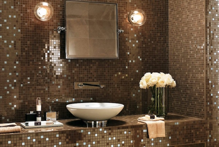 vase with white roses, two lamps and a mirror, and a round white sink, in a room with walls covered in mosaic, in different shades of brown, with tiny mirror details, bathroom wall decor ideas