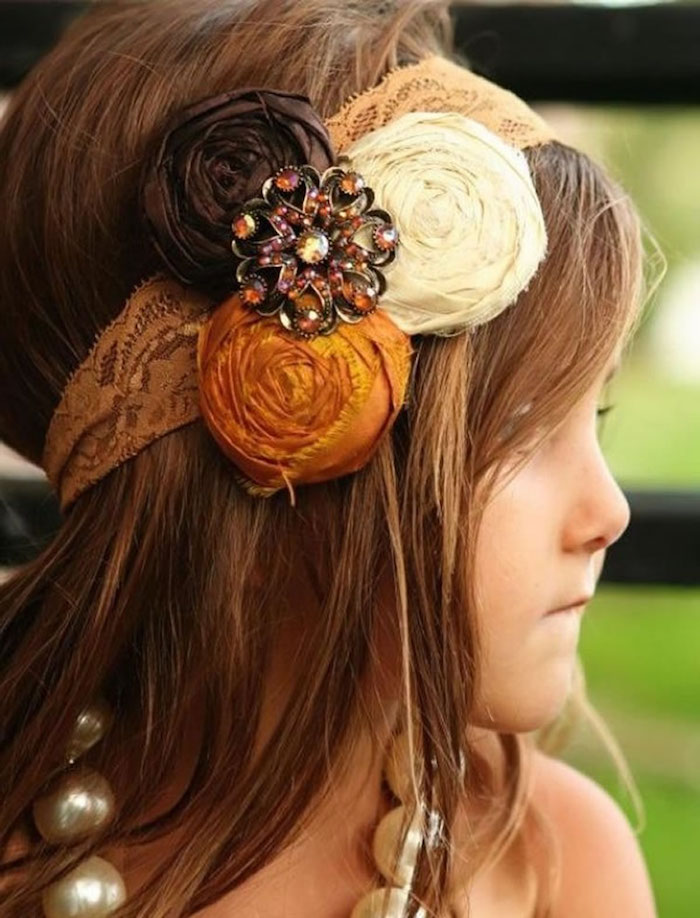 beige lace headband, decorated with flower motifs in orange, cream and dark brown, on the smooth, long brunette hair, of a young child, simple hairstyles, oversized pearl-like necklace