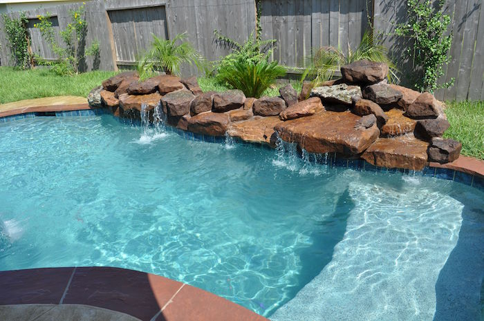 ferns and large brown stones, decorating the side of a pool, placed in a garden, small inground pools, water flowing from the stones