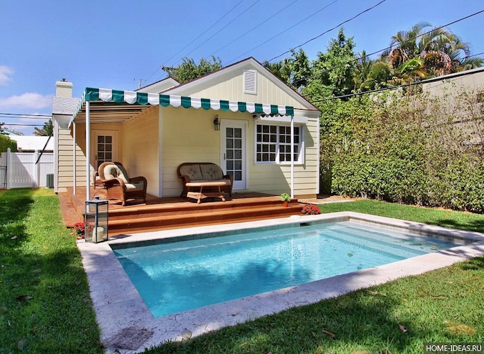 cream colored bungalow, with a small porch, containing two vintage armchairs, small classical rectangular pool nearby