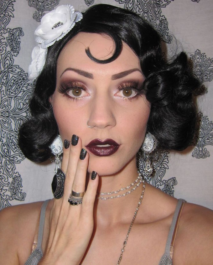 close up of a woman's face, with cherry red lipstick, purple eyeshadow and fake lashes, and black hair, styled in a 1920s bob