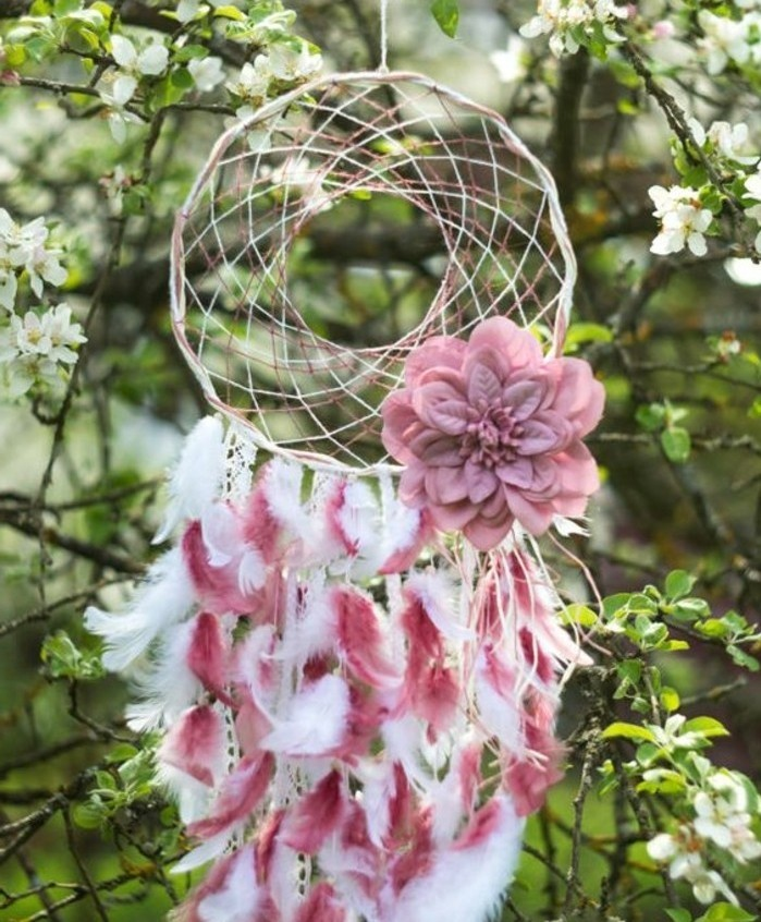 fluffy small feathers, in white and pink, attached to a dreamcatcher, decorated with a pink flower ornament, how to make a dreamcatcher, hung on a blossoming tree