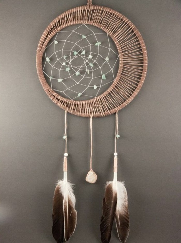 two chocolate brown and white feathers, and a small pink stone, tied to a rattan dreamcatcher, with a white net, decorated with pale blue beads, pictures of dream catchers, on a grey wall