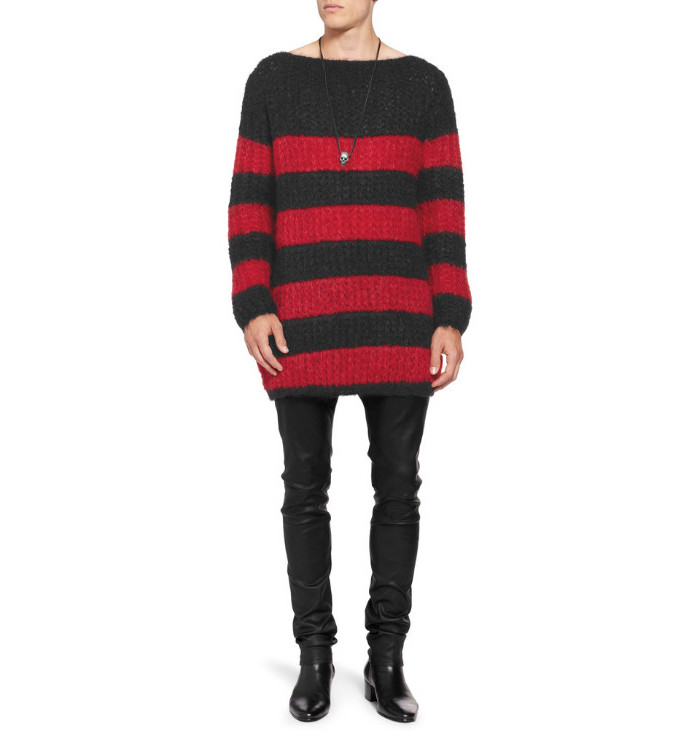 striped red and black, long and baggy knitted sweater, worn by a slim man, in black leather trousers, 90s themed outfits, black ankle boots and skull necklace