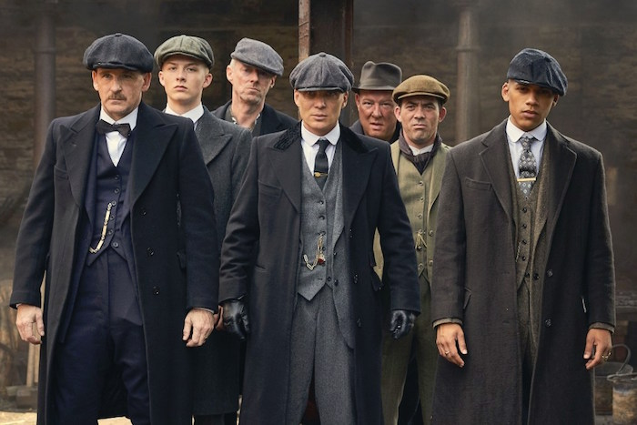 characters from bbc's tv series peaky blinders, dressed in 1920s attire, dark three-piece suits, and wollen caps, great gatsby outfits, woolen winter coats
