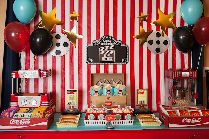 hot dogs and popcorn, on a table, with vintage vending machines, an assortment of sweets, balloons and various film themes decorations, 60th birthday party ideas