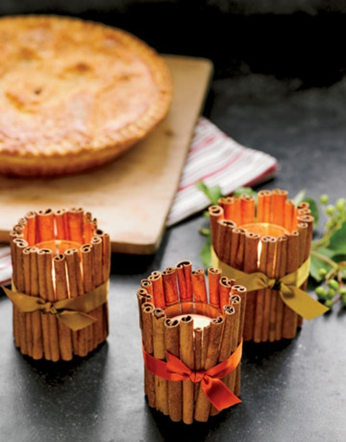 handmade gift ideas, sticks of cinnamon, placed around three candle holders, with lit candles, and tied with gold ribbons, a pie in the background