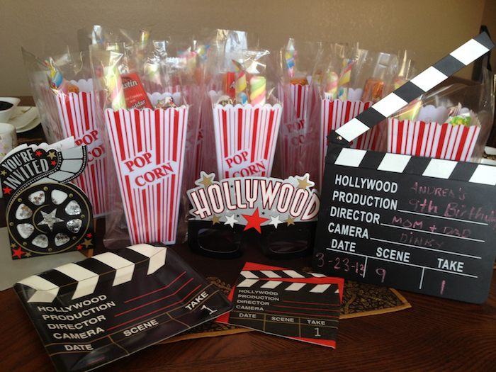 hollywood inspired decorations, like cardboard clapperboards and movie reels, 60th birthday ideas, several vintage-style popcorn boxes, white with red stripes, containing a selection of sweets