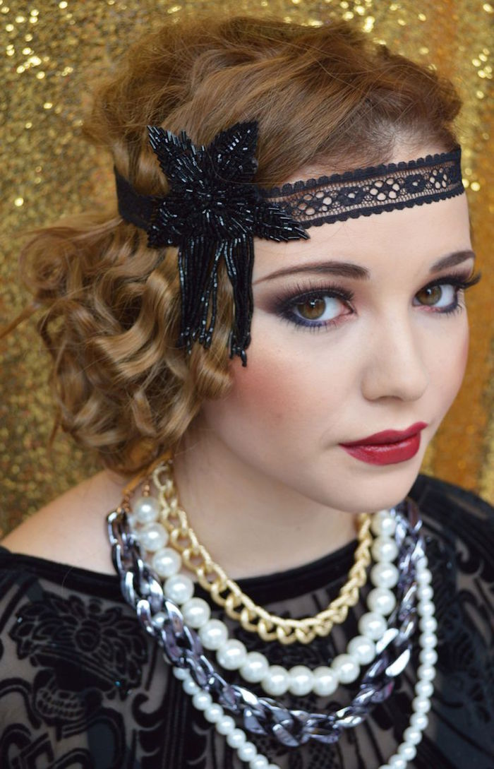 several chunky necklaces, and a black flapper headband, worn by a young woman, in sheer black lace top, and 1920s make up