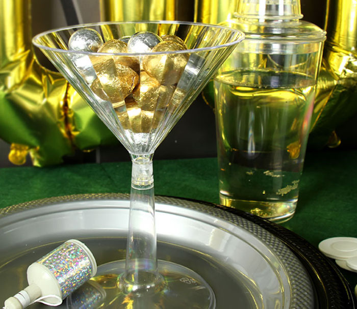 martini glass made from clear plastic, filled with round candies, in gold and silver wrappers, 60th birthday party ideas for men, james bond casino royale theme