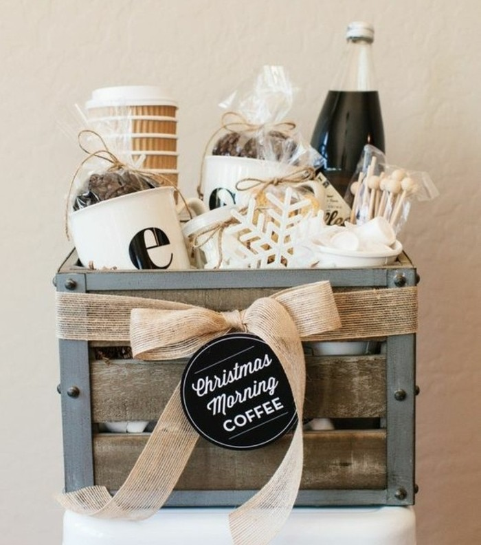 crate made from metal and wood, containing paper cups, packets with coffee beans, cute gift ideas, marshmallows and a bottled beverage