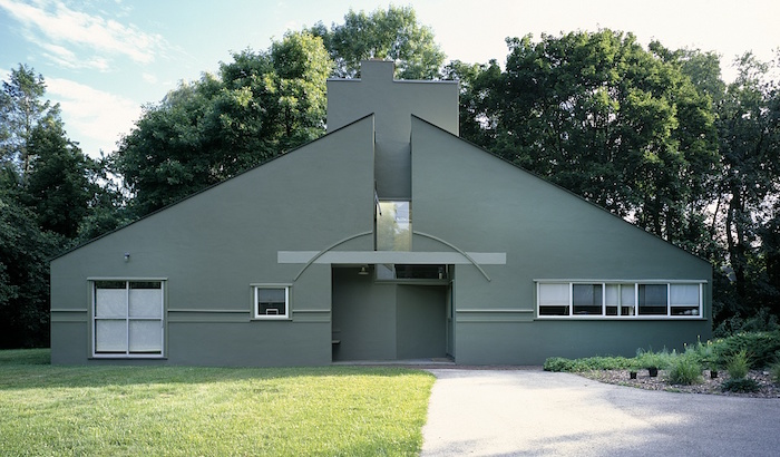 vanna venturi house, with divided gabled roof, and a large rectangular chimney, post modernity, several small and one large window
