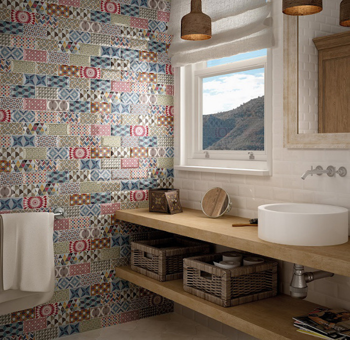 mismatched patterns and different colors, on patchwork-effect subway tiles, covering one of the walls of a nordic-style bathroom