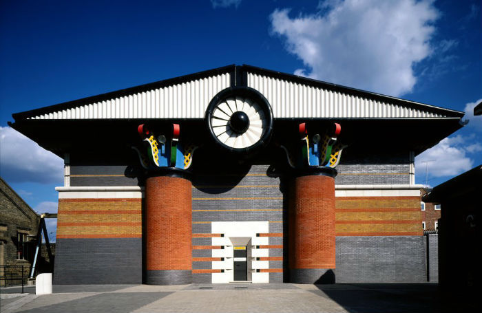 flattened gabled roof in black and white, propped on yellow and grey round columns, decorated with multicolored details on top, postmodernism examples, orange and grey pumping station building