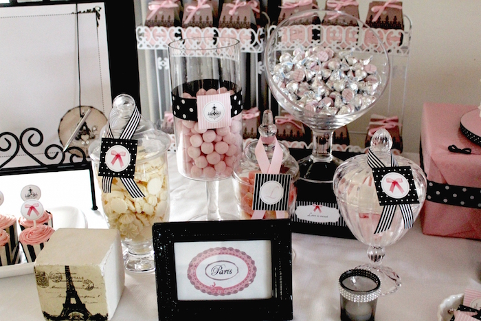 jars and other glass dishes, containing candies in pink, cream and silver, on a parisian-themed party table, 60th birthday party ideas for mom, little eiffel tower decoration