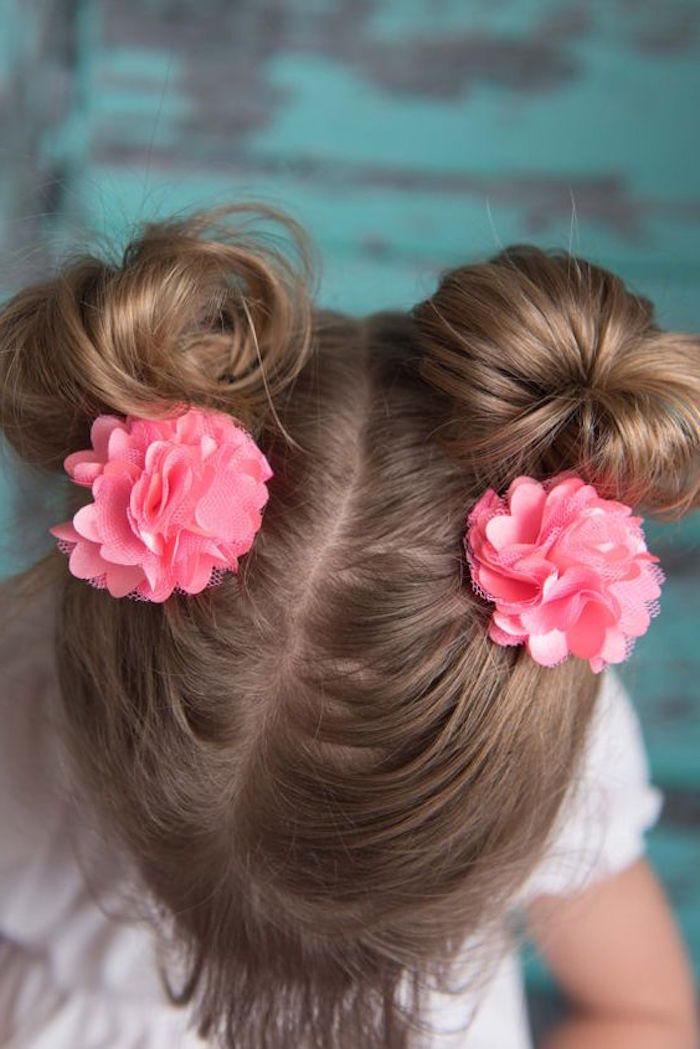 high-angle photo, showing a child's head, with chocolate brown hair, tied in two pigtails, hairstyles for little girls, coral pink flower-shaped hair ornaments