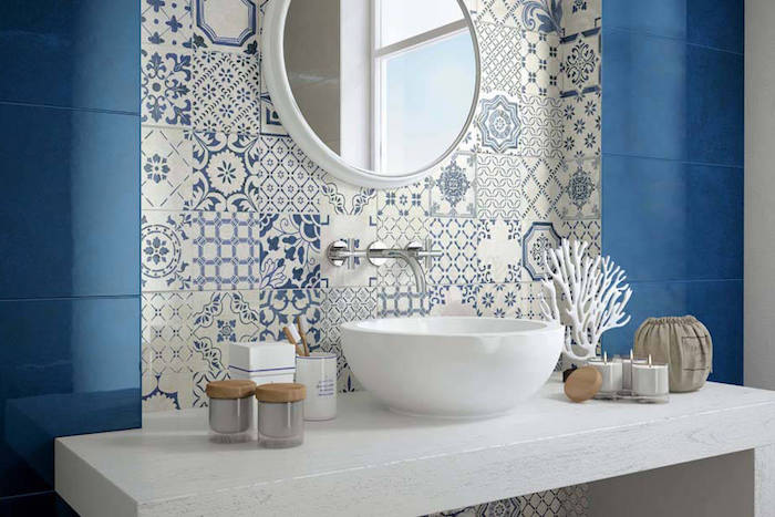 candles and a white, coral-shaped decoration, on a white counter with a sink, diy bathroom décor, near a wall covered in blue, and white moroccan tiles