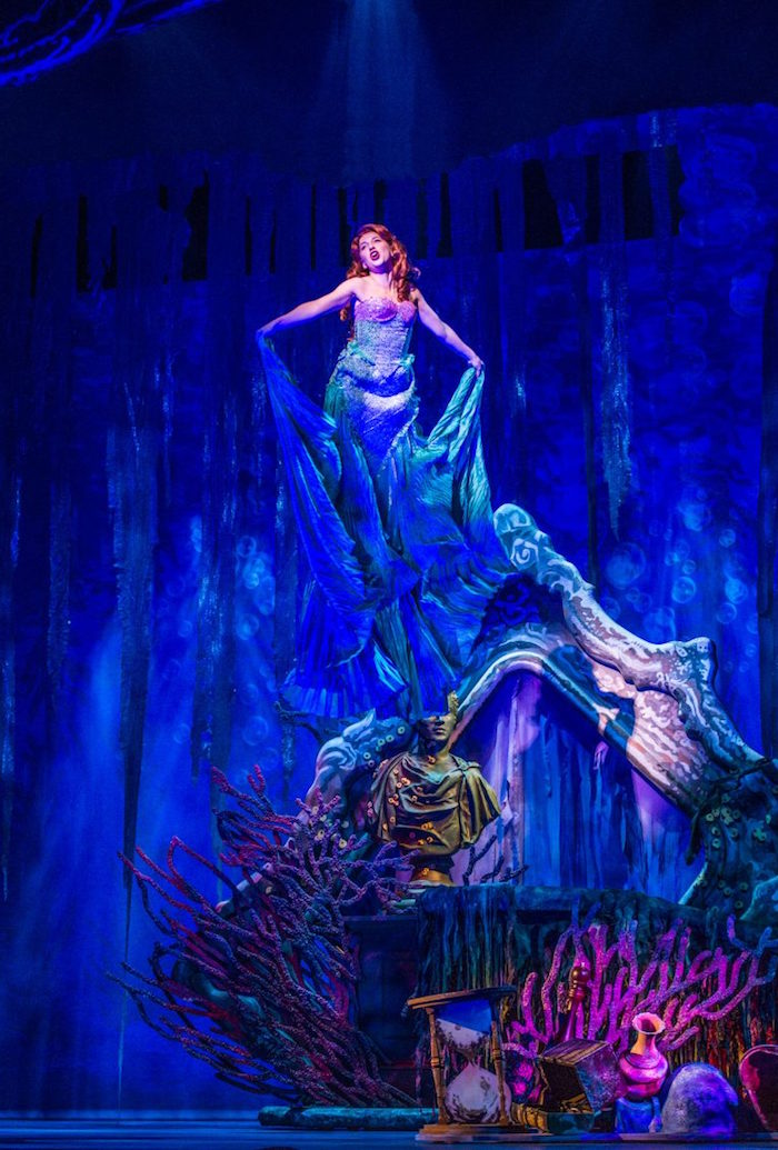 woman in a long blue gown, and red wig, standing on a stage, with elaborate set design, made to look like an underwater world